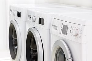 row line of modern white laundry washing machines